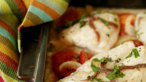 Anchovy-baked fish with tomatoes and onions.
