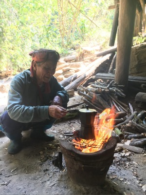 A vendor brewing local coffee beans over an open fire in Thailand's north.