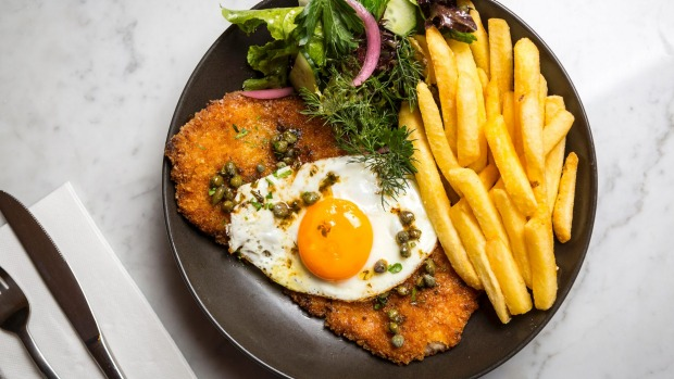 Pork schnitzel with chips, fried egg and capers.