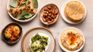 The opening flurry of snacks starring Turkish breads, hummus, and arak cucumbers.
