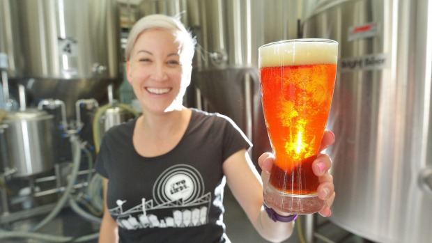 Jayne Lewis from Two Birds Brewing with a glass of Sunset Ale.