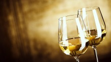 Two glasses of white wine standing side by side.