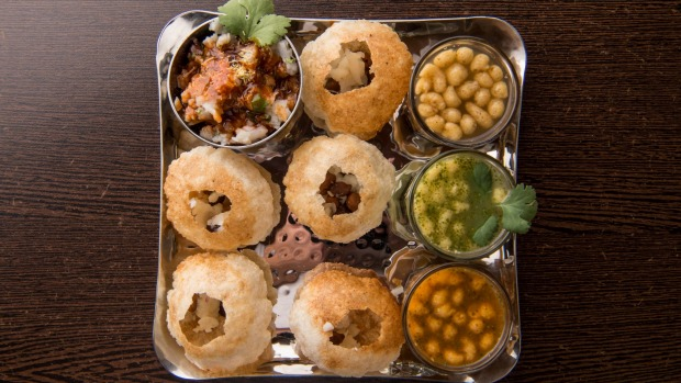Pani puri, crisp shells to be filled with chickpeas, potatoes, chutneys and tamarind water.