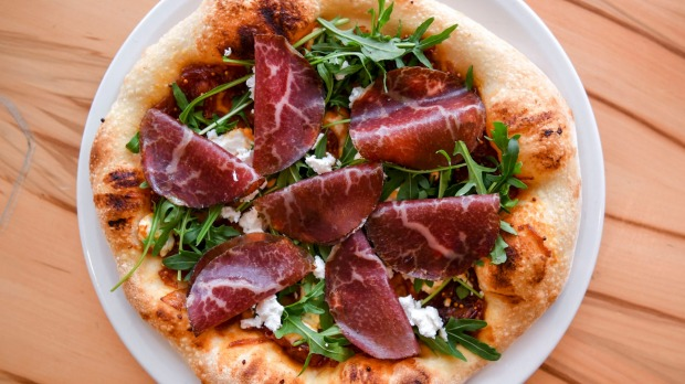 Bresaola pizza with onion, goat's cheese and rocket.