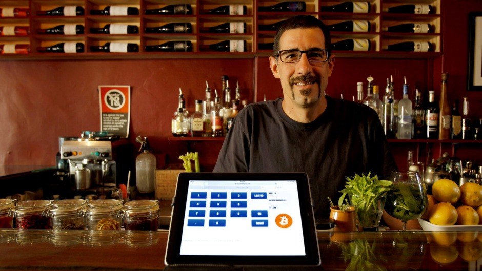 Amir Halpert, the owner of The Owl House in Darlinghurst, shows the bar's bitcoin pay system on his iPad.