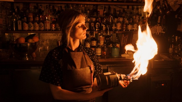 Bar manager Mary White toasts cocktail garnishes with a big butane flame.