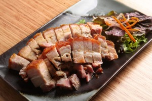 A platter of roasted pork belly with shatter-crisp crackling.