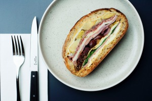 The muffuletta, a pressed baguette of olive, mortadella, salami, ham, provolone, peppers and artichokes.