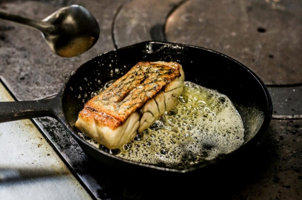 Return the fish to skin-side up and baste the skin with butter.
