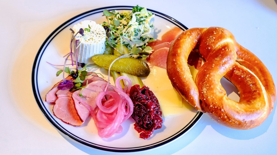 Austro's pretzel plate with cured meats, cheese and pickles.