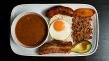 Bandeja paisa platter with braised red beans, chicharron (fried pork belly), minced beef, Colombian chorizo,  plantain, ...