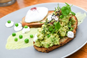 Avocado smooshed with peas and lime on sourdough.