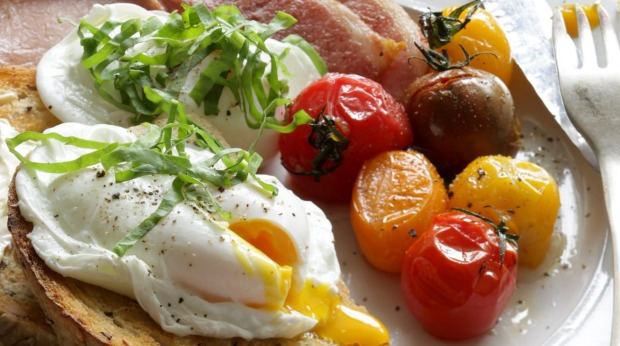 Poached eggs with roasted tomatoes, bacon and shaved sorrel.