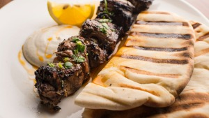 Skewered lamb rump with grilled flatbread and a squeeze of lemon.