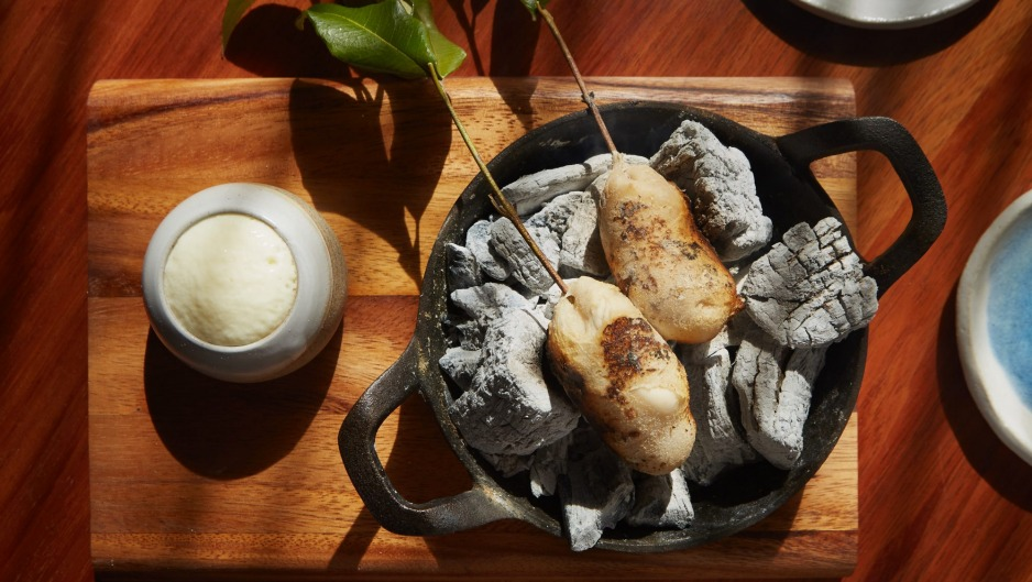 Potato damper on eucalyptus skewers, cooking on hot coals at your table.