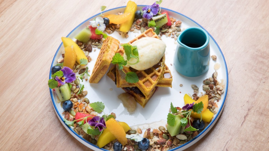 Spiced pumpkin waffle encircled by fruit, nuts and seeds.