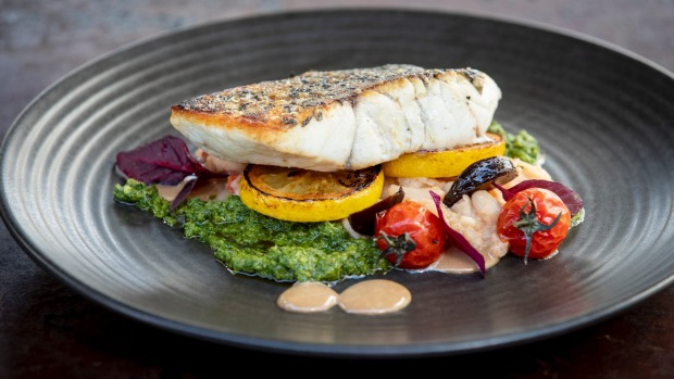 Barramundi with whitebean and fennel cassoulet, salsa verde, black garlic and tomatoes.