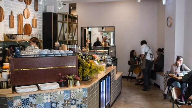The Bells Road Social's counter features a patchwork of tiles and a display of chopping boards.
