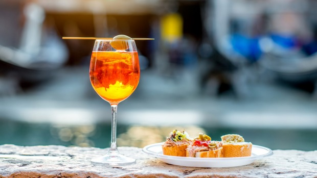 Aperol spritzwith cicchetti(traditional Venetian snacks)on the canal in Venice.
