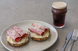 A pastrami bagel with nitro cold brew.