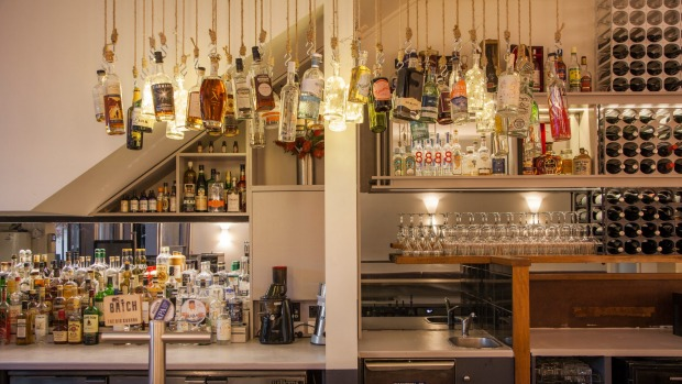 Bottles swing above the bar at Rosenbaum & Fuller, Bondi.