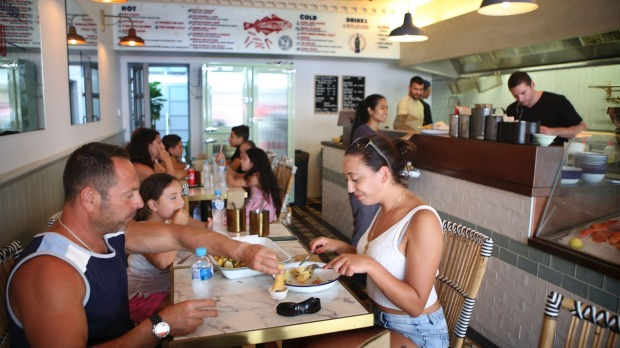 Patrons enjoy fresh fish and chips from 'The Fish Joint' Cafe at Brighton Le Sands.