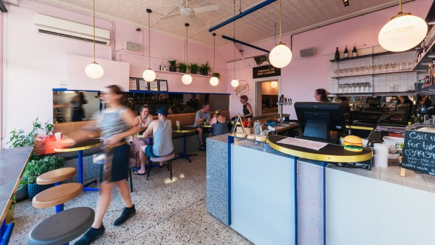 Slider Diner's interior features bright pastels, touches of brass and terrazzo.