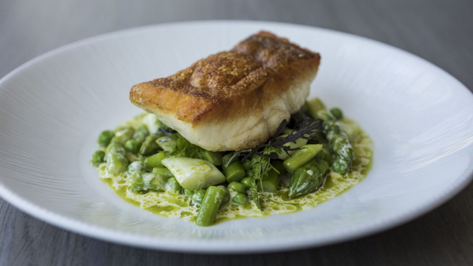 Coral trout is served crisp-skinned atop peas and asparagus.