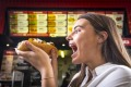 Alice Macmillan from South Yarra enjoys one of the vegan hot dogs at Lord of the Fries, Windsor.