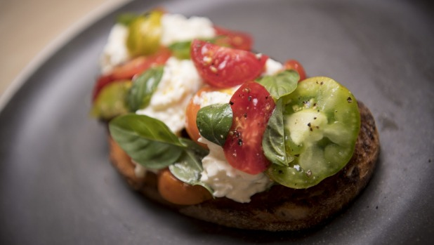 Stracciatella cheese, heirloom tomatoes and basil on sourdough toast.