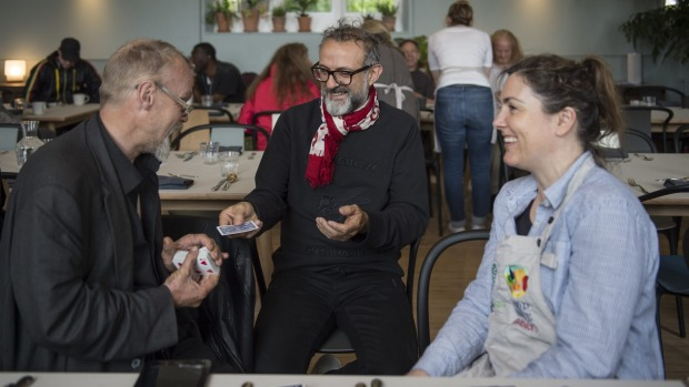 Massimo Bottura playing cards with diners at Refettorio Felix in London.