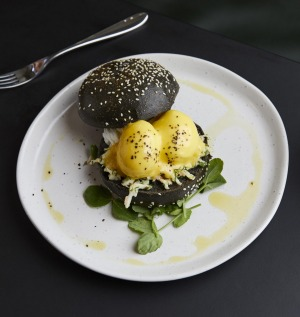 Lobster benedict with citrus hollandaise, soft herbs, a black bun and 64-degree eggs.