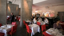 Videos and slashes of vivid red electrify the Di Stasio Citta dining room.