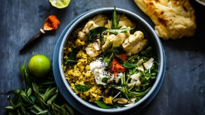 Far from blah: Colourful Sri Lankan curry-poached chicken and rice with salad, condiments and optional naan bread.