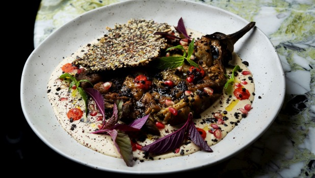 Fire-roasted eggplant, with tahini, fermented chilli, baby leaves and olives.