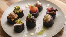 Purple rice nori rolls are sliced and garnished like nigiri-sushi hybrids.