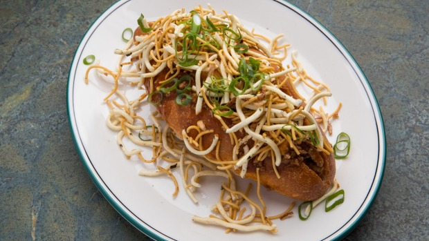 Mapo tofu and noodle bun with fried noodles and spring onion.