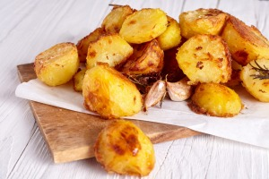 Partly cook potatoes before tossing in fat and roasting for a crisp finish.