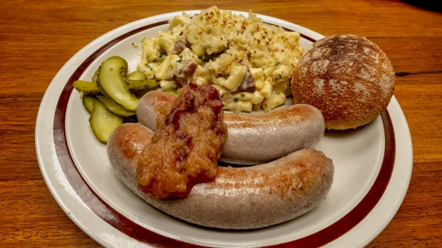 Free-range pork sausages with apple and cranberry relish, pickles and macaroni cheese.