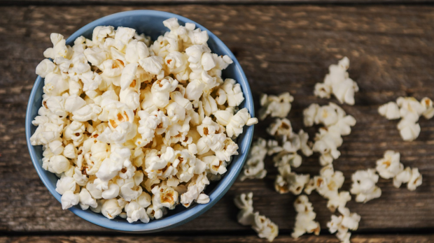 Popcorn in a blue bowl on wooden table Healthy late-night snacks Crudites, vegetable sticks, dips, dip Popcorn, Trail mix iStock photos