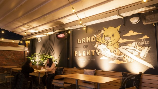 A mural of Wade the Wombat by Australian artist LeGrizz covers one wall at Land of Plenty, St Kilda.