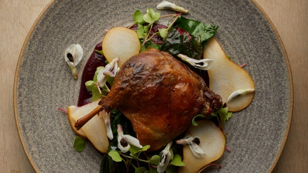Confit duck leg with pears and broad bean flowers.