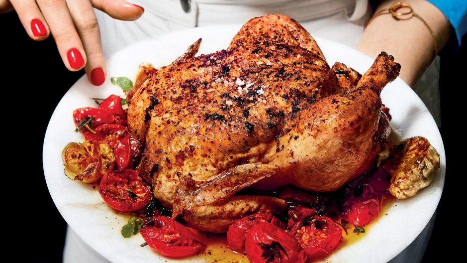 Roman's signature red nailsand roast chicken star on the cover of her second cookbook, Nothing Fancy.