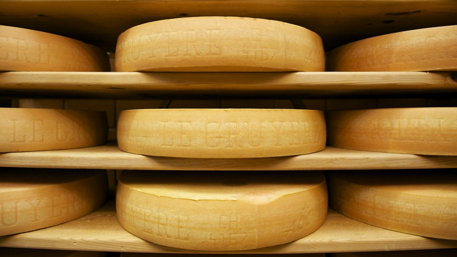 Wheels of Switzerland's most famous cheese matures on wooden shelves in Gruyeres.