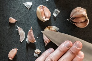 Place a garlic clove on a chopping board, lie the flat blade of a knife on top and give the knife a firm blow with the ...