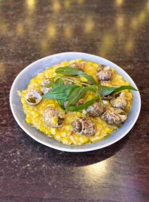 Oc huong (spotted Babylon snails) on butter-drenched sweet corn.