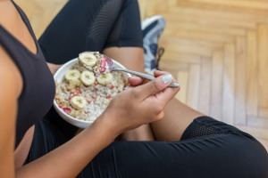 Young woman eating a oatmeal after a workout Exercising before breakfast leads to greater weigh loss, new research shows.