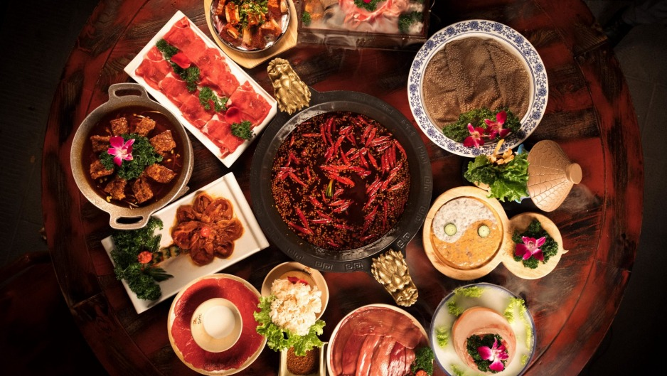 The signature hot pot surrounded by premium cuts of meat and offal for dipping.