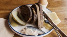 A Cornersmith plate with mackerel, gherkins, boiled egg and bread.