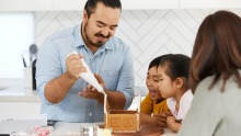 Adam Liaw and his family making a Christmas gingerbread house.